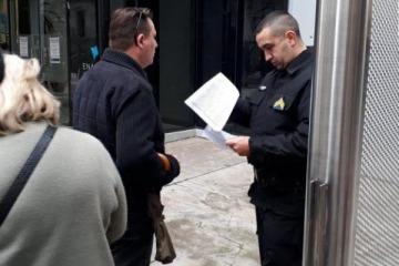 Policías y seguridad privada leen la lista de despedidos en la puerta del ENACOM